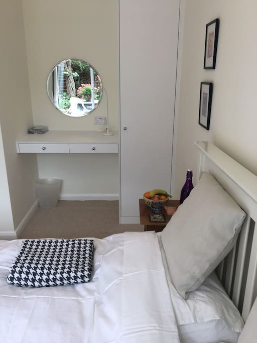 Wardrobe and desk area next to comfortable double bed and with smart TV