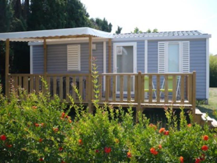 Terrasse avec mobilier de jardin et transats.