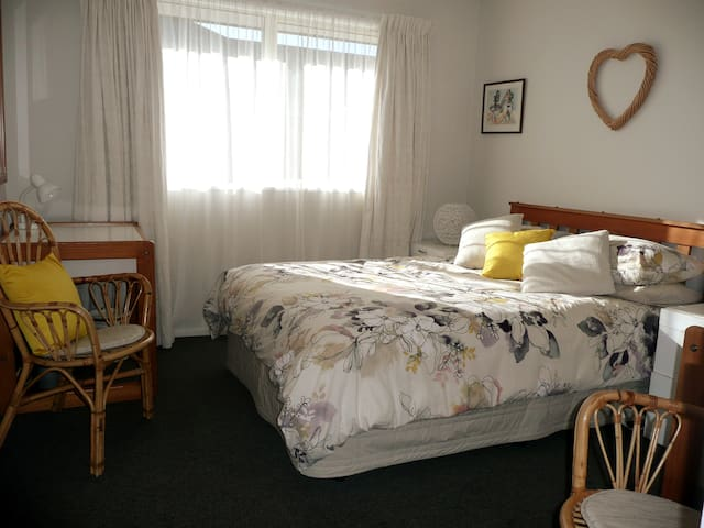 Double bed in roomy bedroom with 2 desks and chairs.