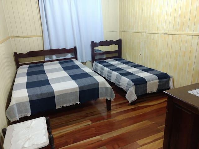 Quarto dois. Nesse quarto temos uma cama de casal e uma de solteiro. Ainda temos uma escrivaninha