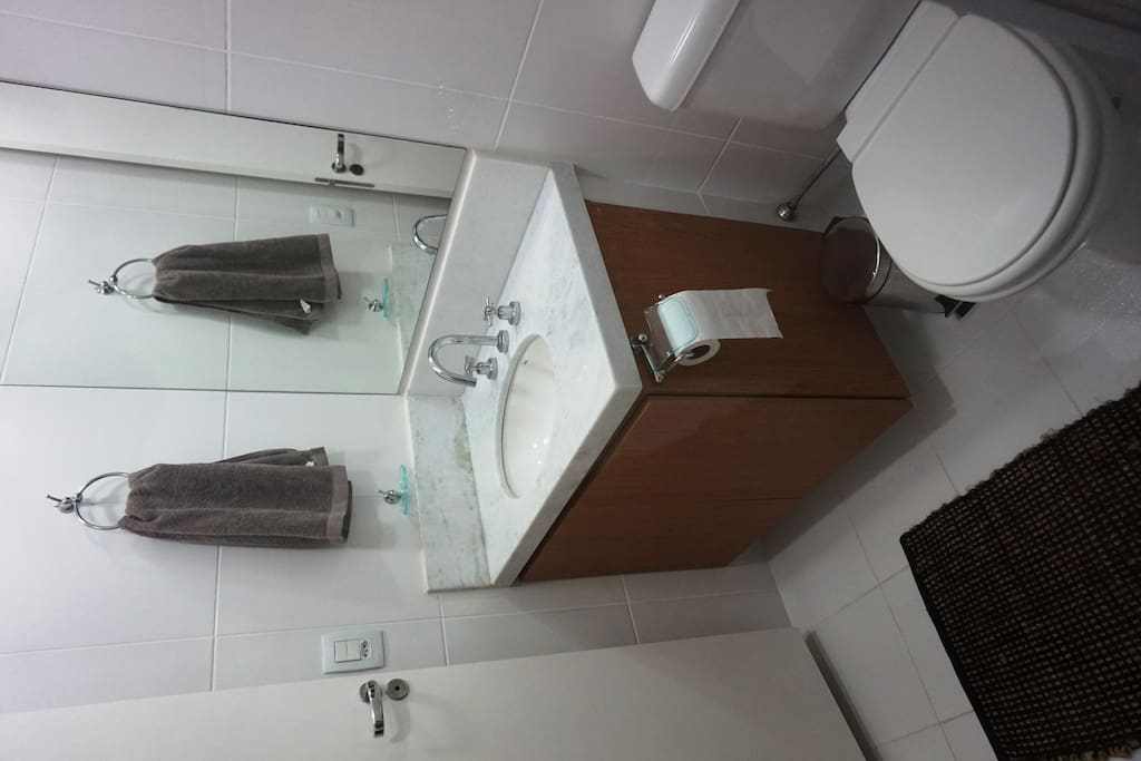 banheiro suite solteiro com roupa de banho, produtos de higiene pessoal e tapete
