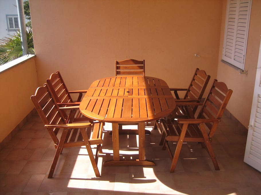 Large balcony with table and chairs.