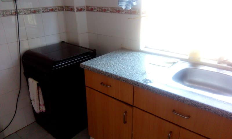 Clean, spacious kitchen with adequate storage cabinets, microwave, fridge and gas cooker with oven and grill