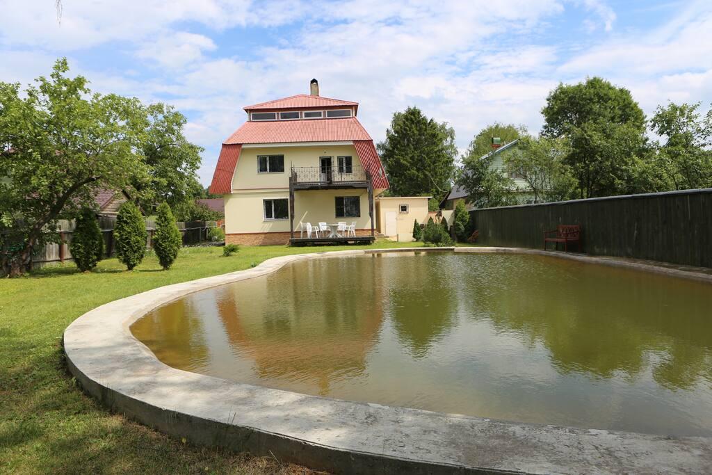 Вид уютного дома с прудом