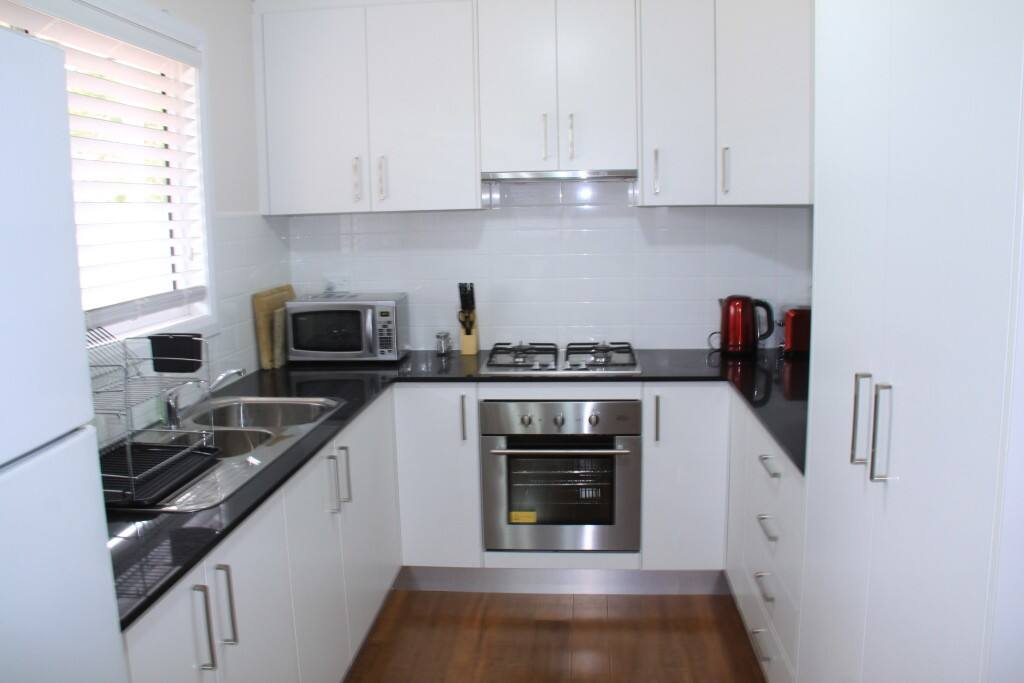 Fully-equipped caesarstone kitchen with gas hob and full oven.