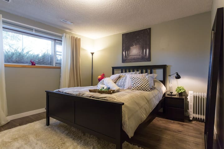 Bedroom with a Queen bed, dresser and night tables, welcome gift included.