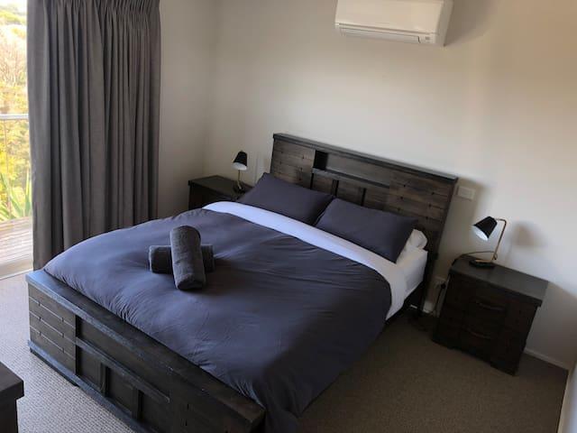 Bedroom 4: A queen bed with ensuite, walk in robe & smart TV