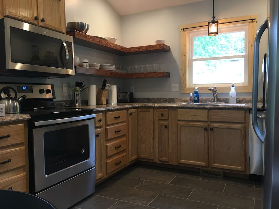 Fully equipped kitchen with microwave, range, oven and refrigerator.