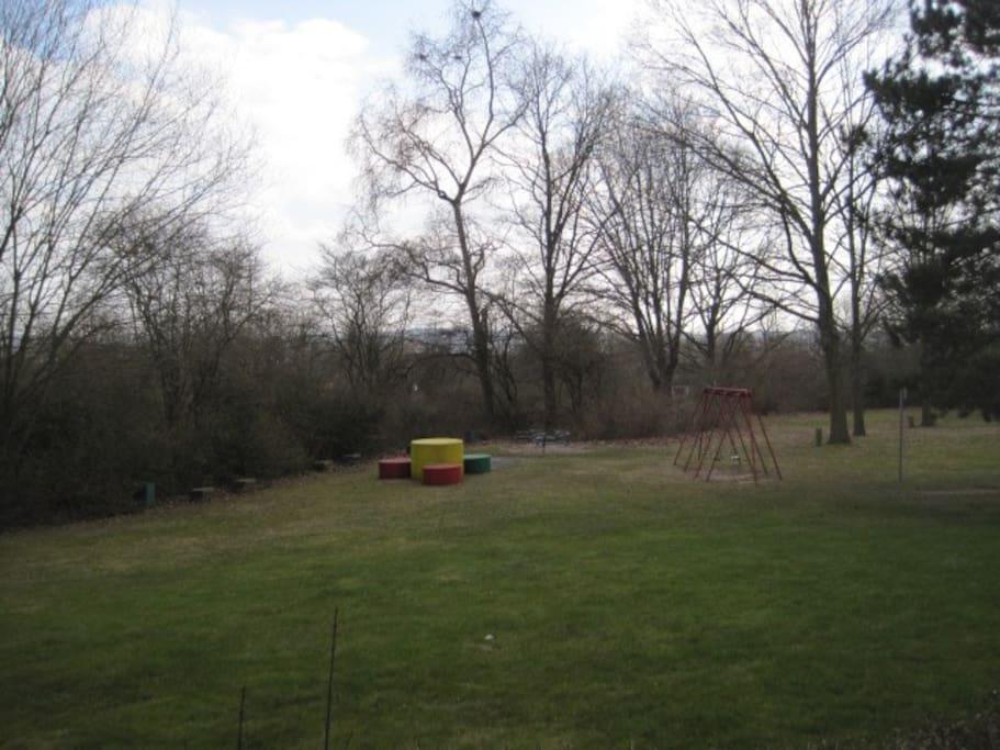 Blick vom Balkon hinters Haus; links vom Haus gibt es einen Kinderspielplatz