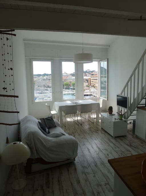 Living/dining area. Dining table overlooks the harbour.