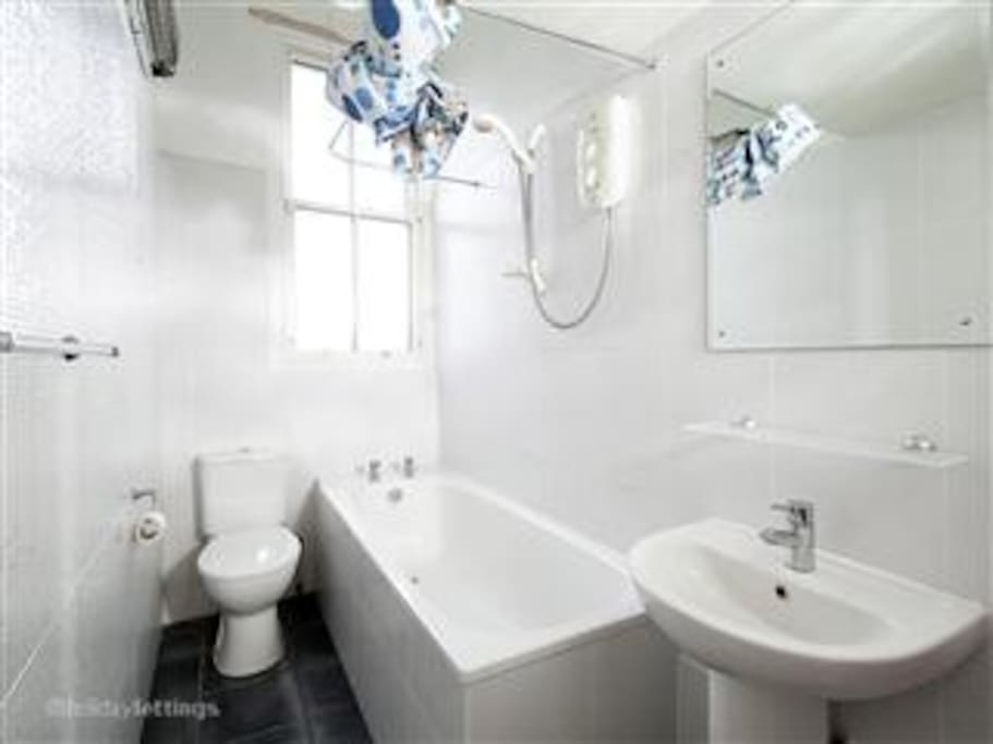 Modern bathroom with shower, bath, window, heater