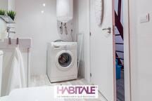Baño completo con lavadora, plancha, tabla de planchar, utensilios de limpueza, toallas, papel higiénico, jabon y champu.