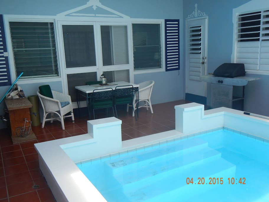 the shallow end of the pool, looking at the dining table and the kitchen door [behind and adjacent to the gas grill]