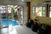 Living Room Seating Area with View To Private Pool and Waterfall