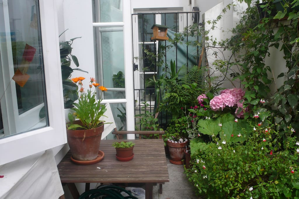 Patio with table and 2 chairs, leads to private enclosed garden