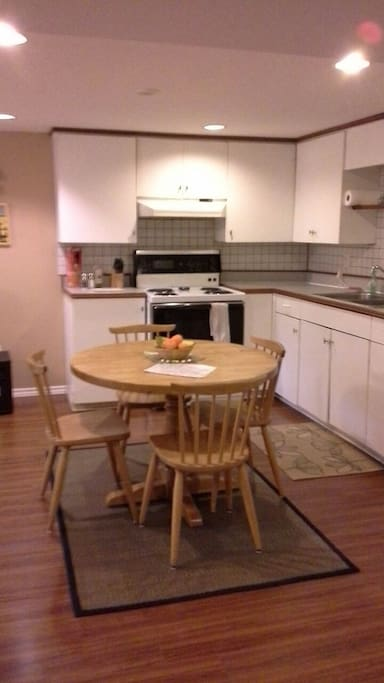 Open concept kitchen, oak table and chairs, electric stove, lots of cupboards,  double sink, full sized fridge