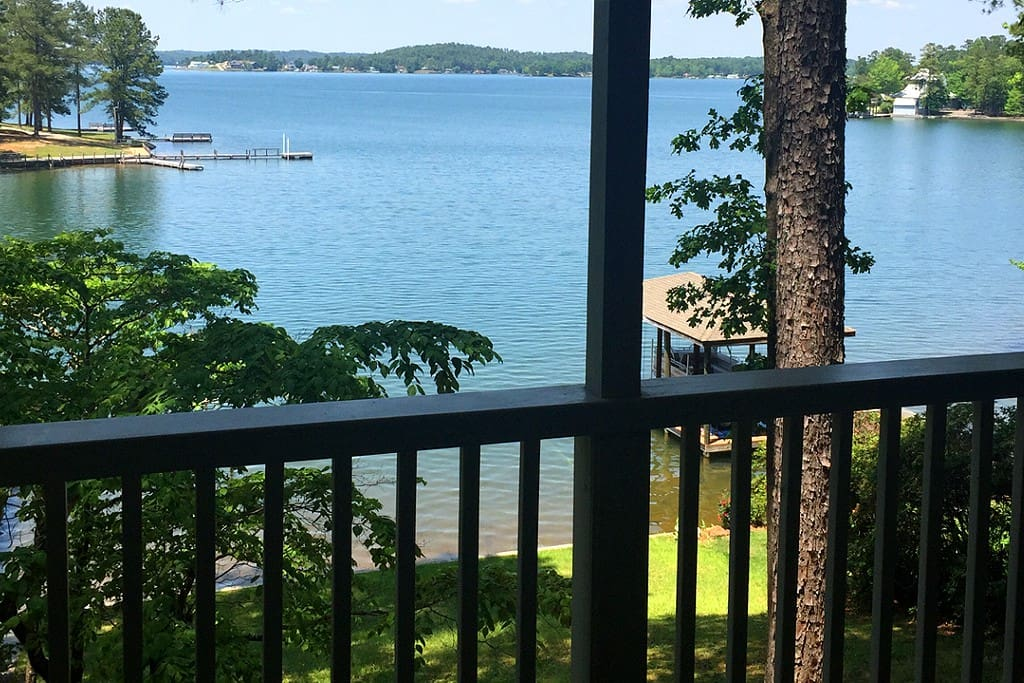 Relax on the porch with beautiful views of Lake Martin, private shoreline and boat dock. Our private HOA boat ramp and family oriented park right across the slough that you see in this photo is a nice place to swim to.