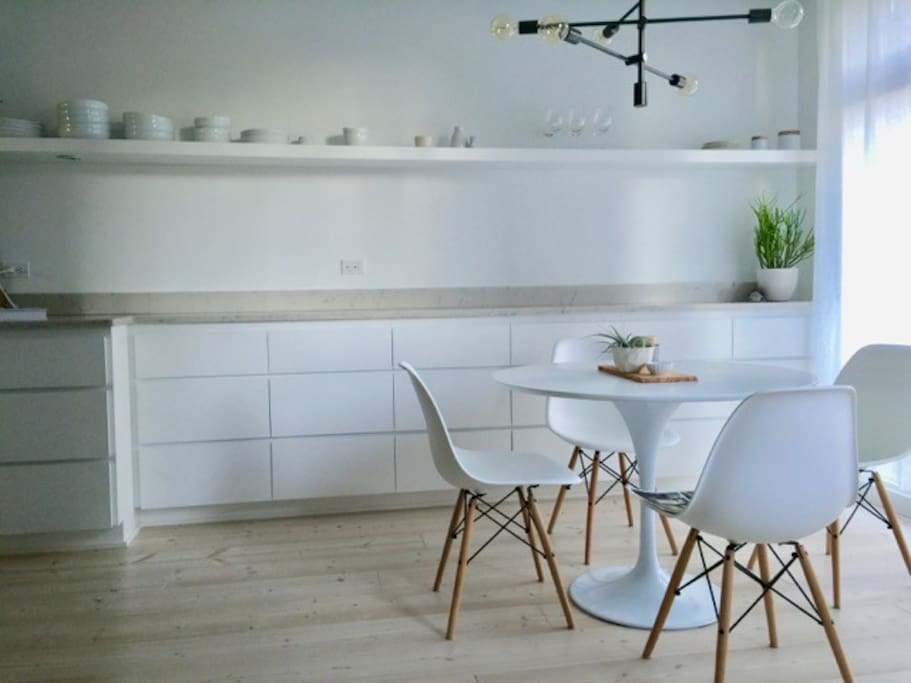 Dining room and bright white kitchen with open shelving.
