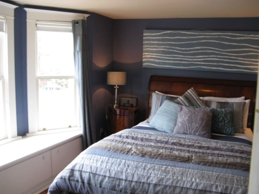 Our Niagara Room with a large bay window overlooking Prideaux Street with horse-drawn carriages, a queen sized bed, two seating chairs, a fireplace and an ensuite bathroom.