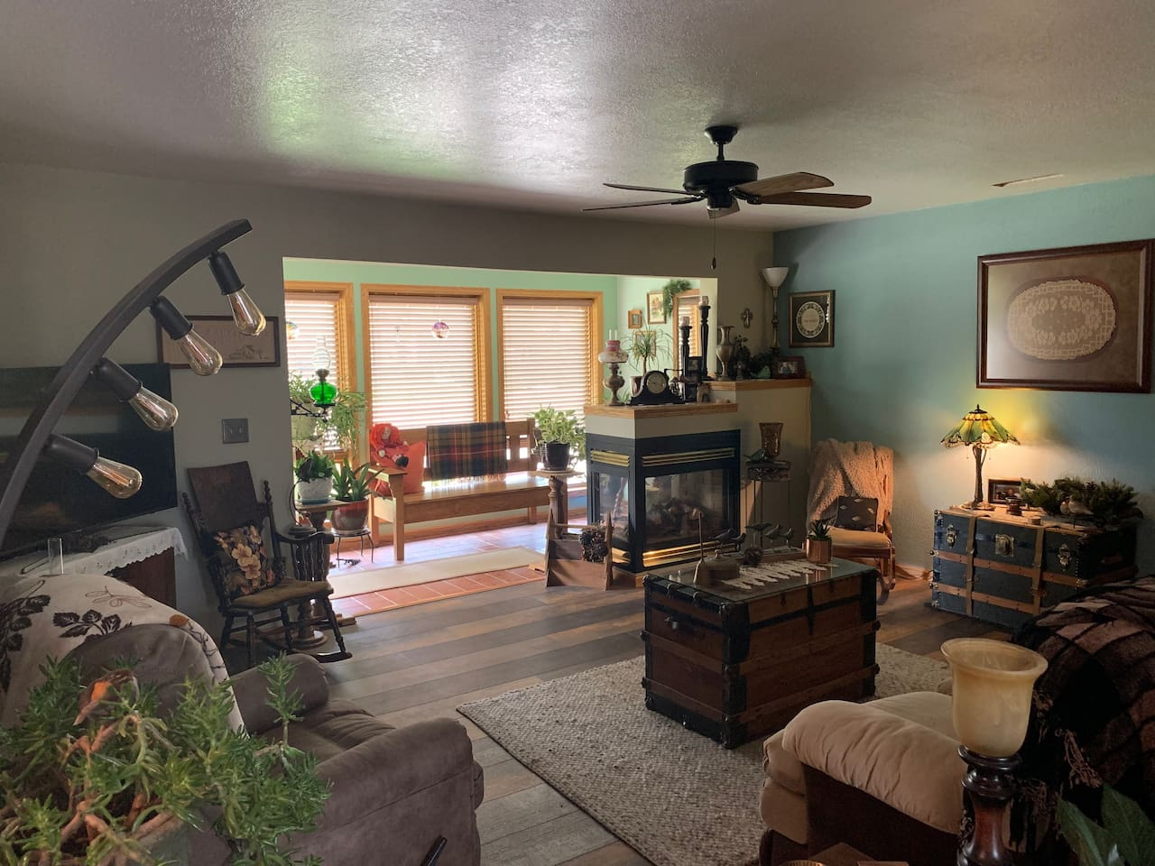Comfortable living room with gas fireplace, big screen TV, ample seating, and sun room overlooking front yard and street.