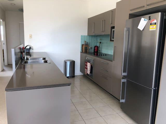 Large open kitchen with plenty of space for preparing food. Dishwasher, microwave, recycling, oven and cooktop, plenty of space in the fridge and freezer as well as cupboard space. Complimentary tea and coffee with milk and sugar.