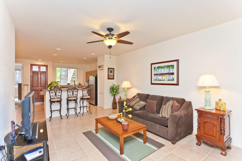 Open floor plan - living room has flat screen tv, comfortable full size sofa sleeper, and teak coffee table.