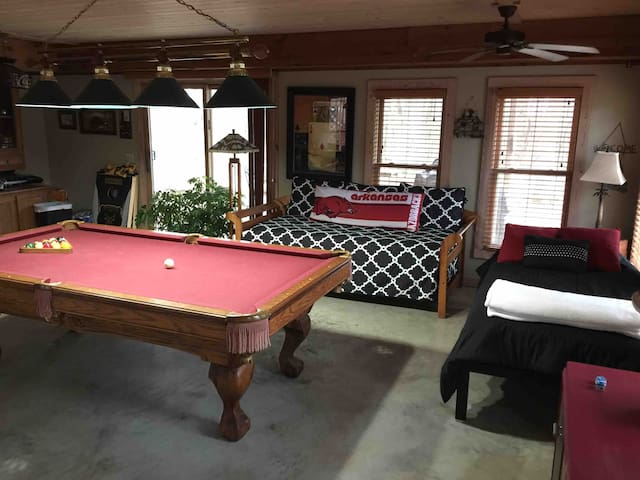 Game room with two single beds. Half bath is off game-room.  (Full bath upstairs). Patio door opens with gas and charcoal grills .   Pots and pans are available in antique ice box on patio .
