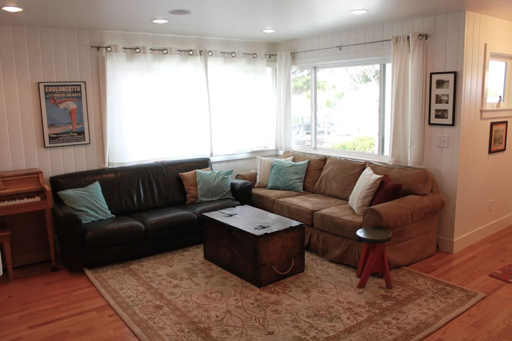 The living area has comfy couches, a piano, and a TV with a DVD player and Apple TV.