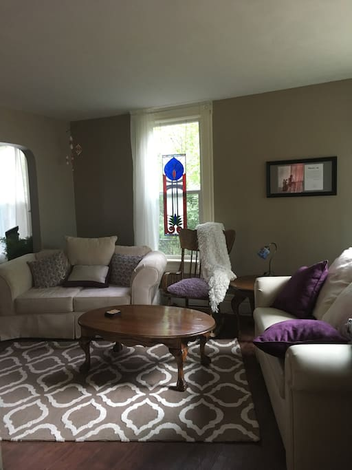 The living room welcomes you with plenty of light, a Smart TV, and two couches.