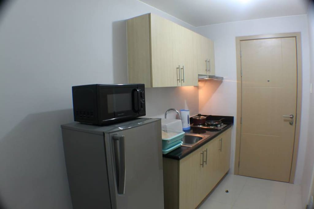 Upon entering the room you will see a very tidy  kitchen set with a refrigerator and microwave oven.