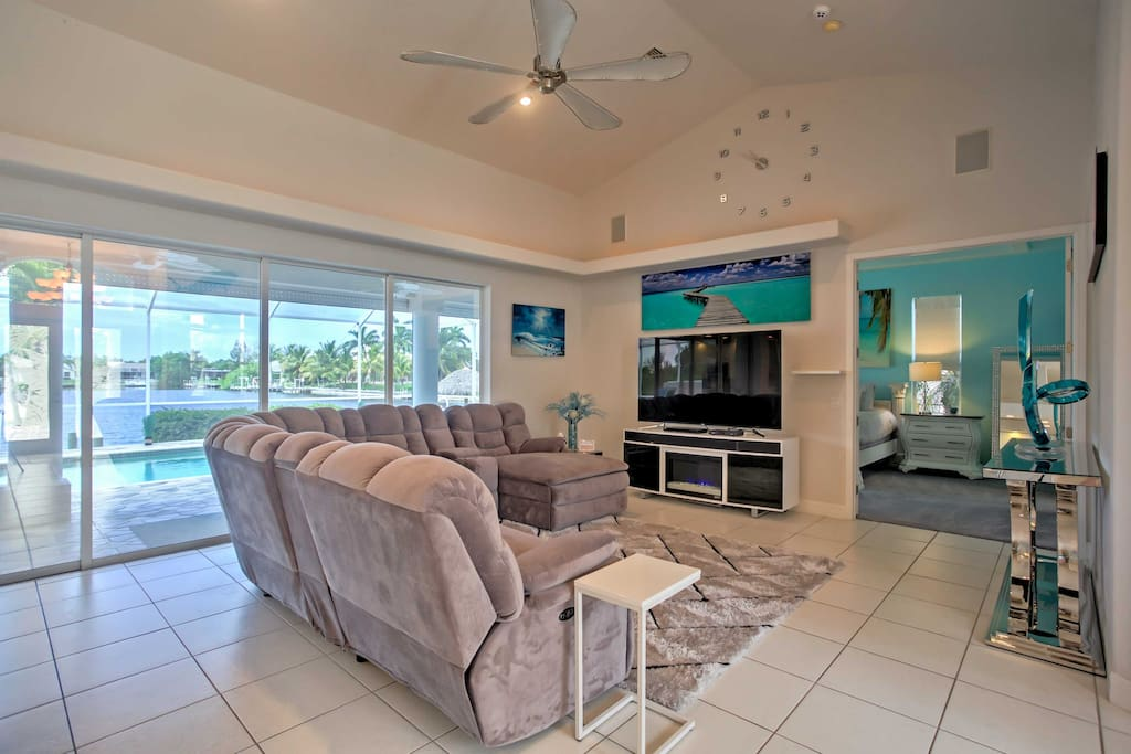 The living room includes a massive reclining sectional and a large, 75-inch flat-screen cable TV, perfect for the family to enjoy a movie together at the end of the day.
