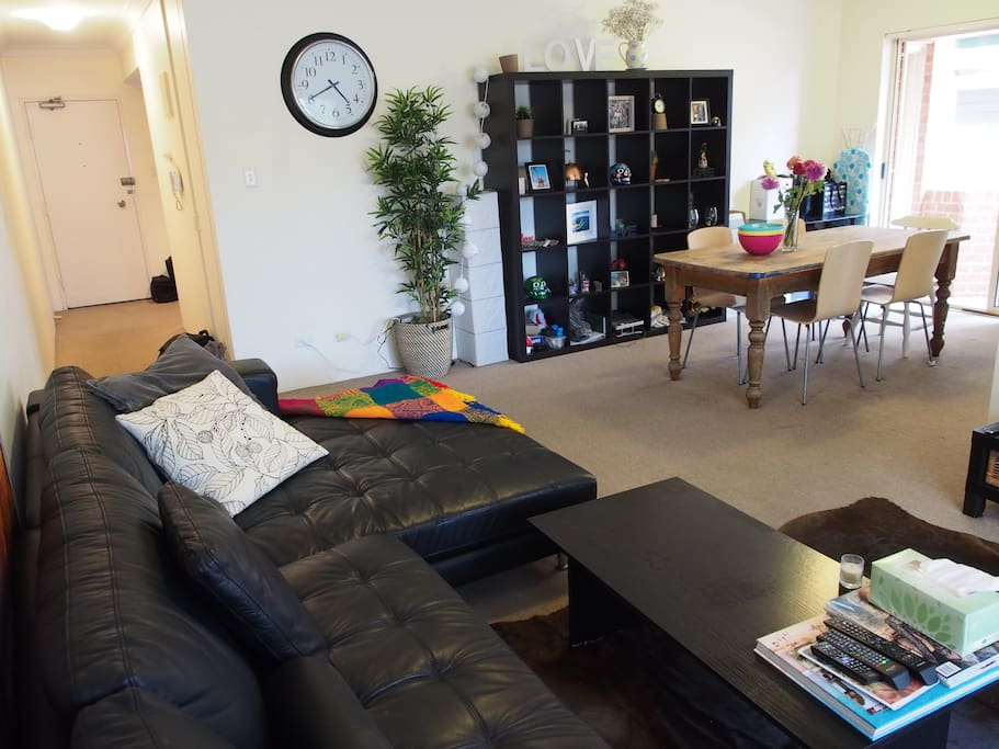 Living room with large leather couch, 6 seater dining table and 65' flat screen TV.