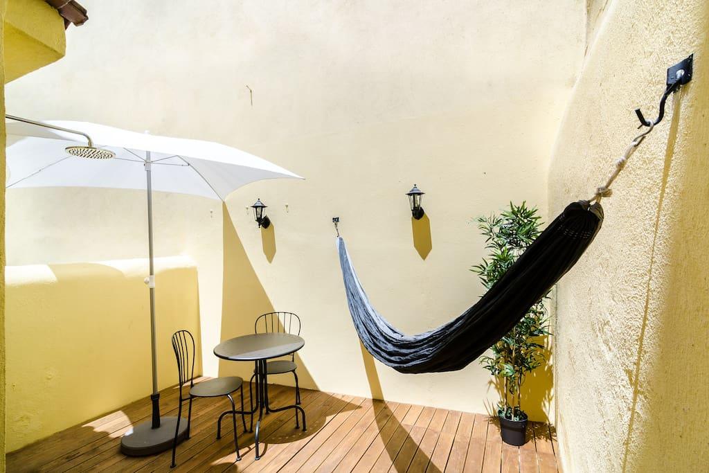 Terraço muito agradável e soalheiro, com rede, mesa e cadeiras, chapeu de sol e ainda chuveiro exterior para se refrescar no verão