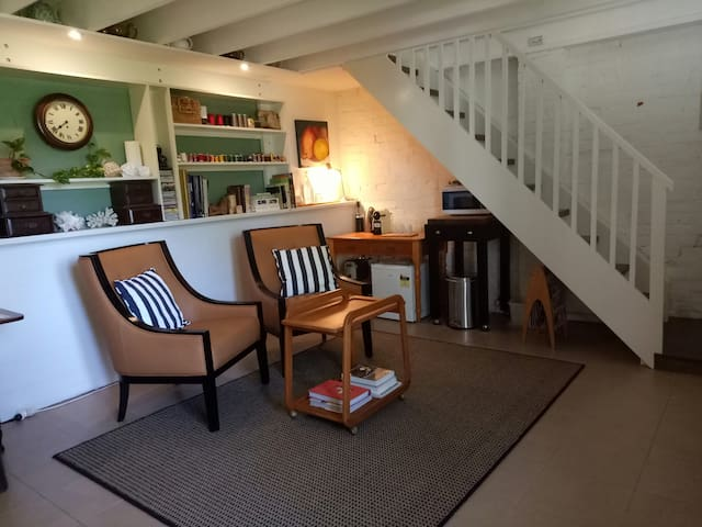 Sitting area with stairs to bedroom. Under the stairs, for your convenience, is a toaster, microwave, electric jug, coffee maker, fridge, quality cutlery and crockery. Tea, coffee, sugar and fresh milk are also provided.