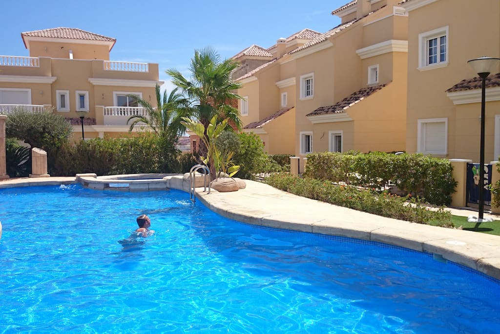 The spacious common pool in a beautifull garden with palmtrees and other plants
