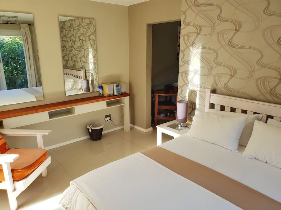 Mirrors, Sound System, Double Bed and Lounge chair in Bedroom