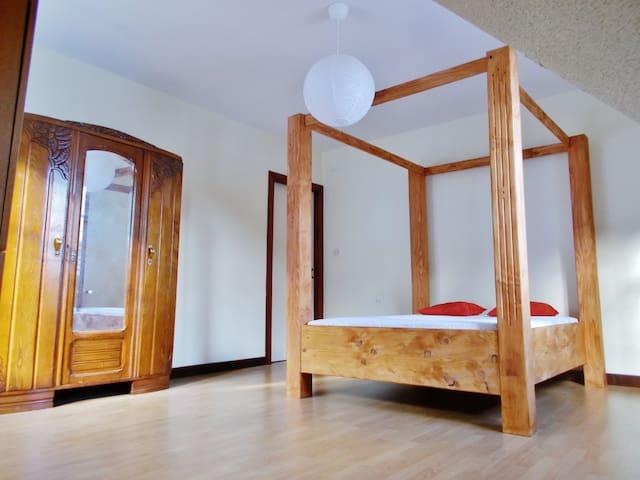 Dépaysement et romantisme assuré avec une nuit dans un lit à baldaquin entièrement fait maison en bois massif ! Une des deux fenêtres donne plein Sud sur le paddock des chevaux !