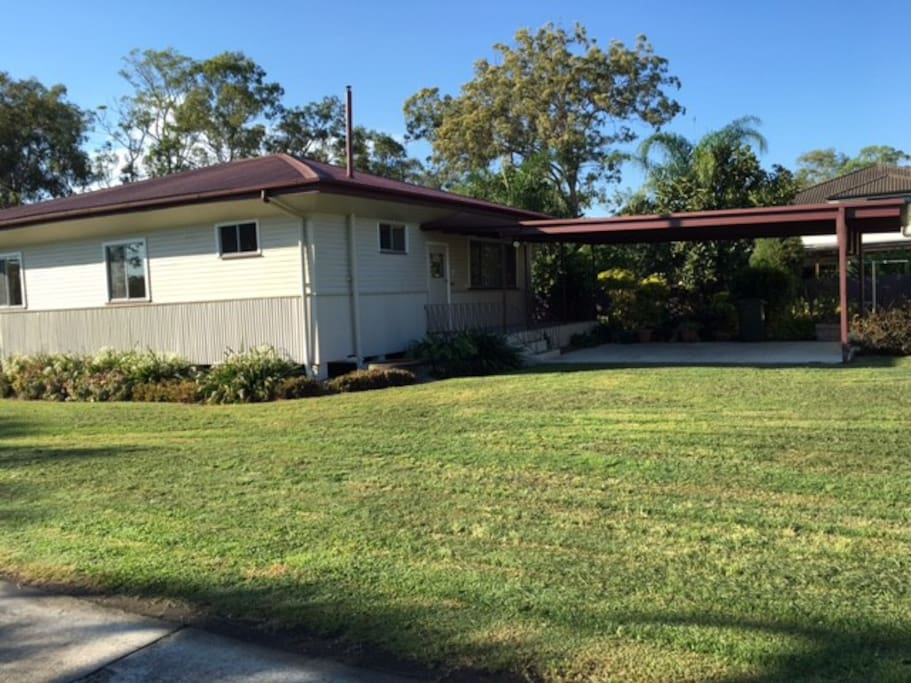 House exterior with carport for 2 vehicles - with plenty of yard for the family.