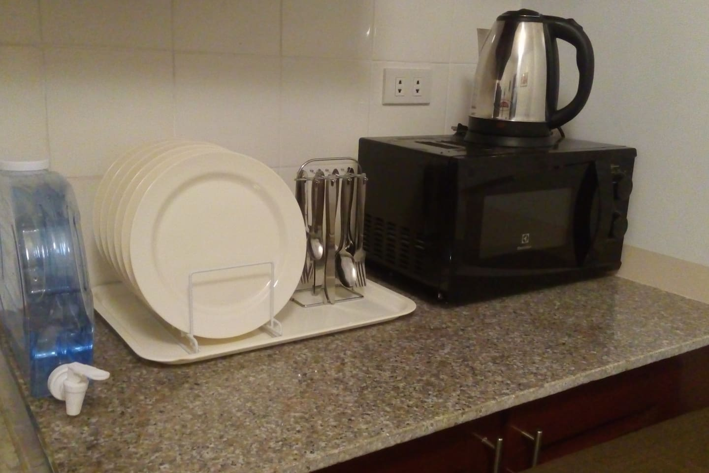 Microwave oven, electric kettle, dining utensils and refrigerator are all provided