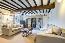 The spacious living room in Lupin Cottage with Freeview TV, sofa bed and traditional fireplace which dominates the far wall.