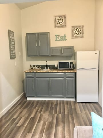 The Kitchen - includes refrigerator, microwave, plates, utensils, toaster, coffee maker and coffee.