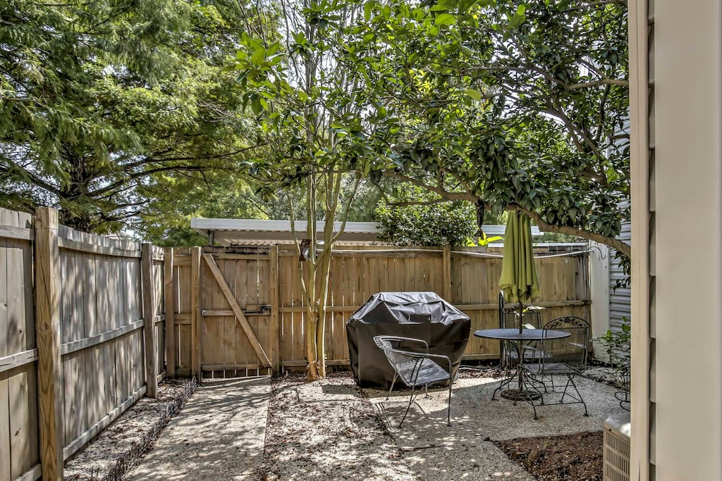 Host a barbecue in the private yard that features an outdoor dining table and gas grill.