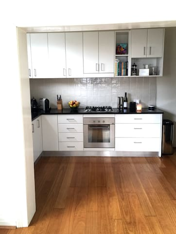Bright open kitchen off living area. Featuring a gas stove top, microwave, fridge, dishwasher, stone bench tops and everything needed to cook up your feast.