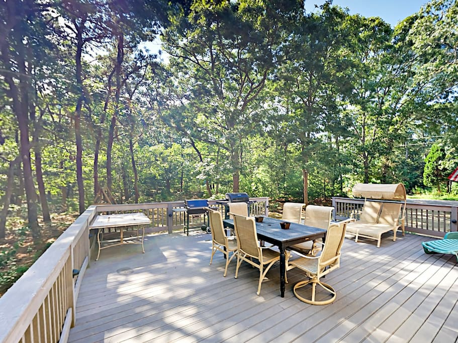 The spacious deck includes ample lounge seating, al fresco dining, and forested surroundings.