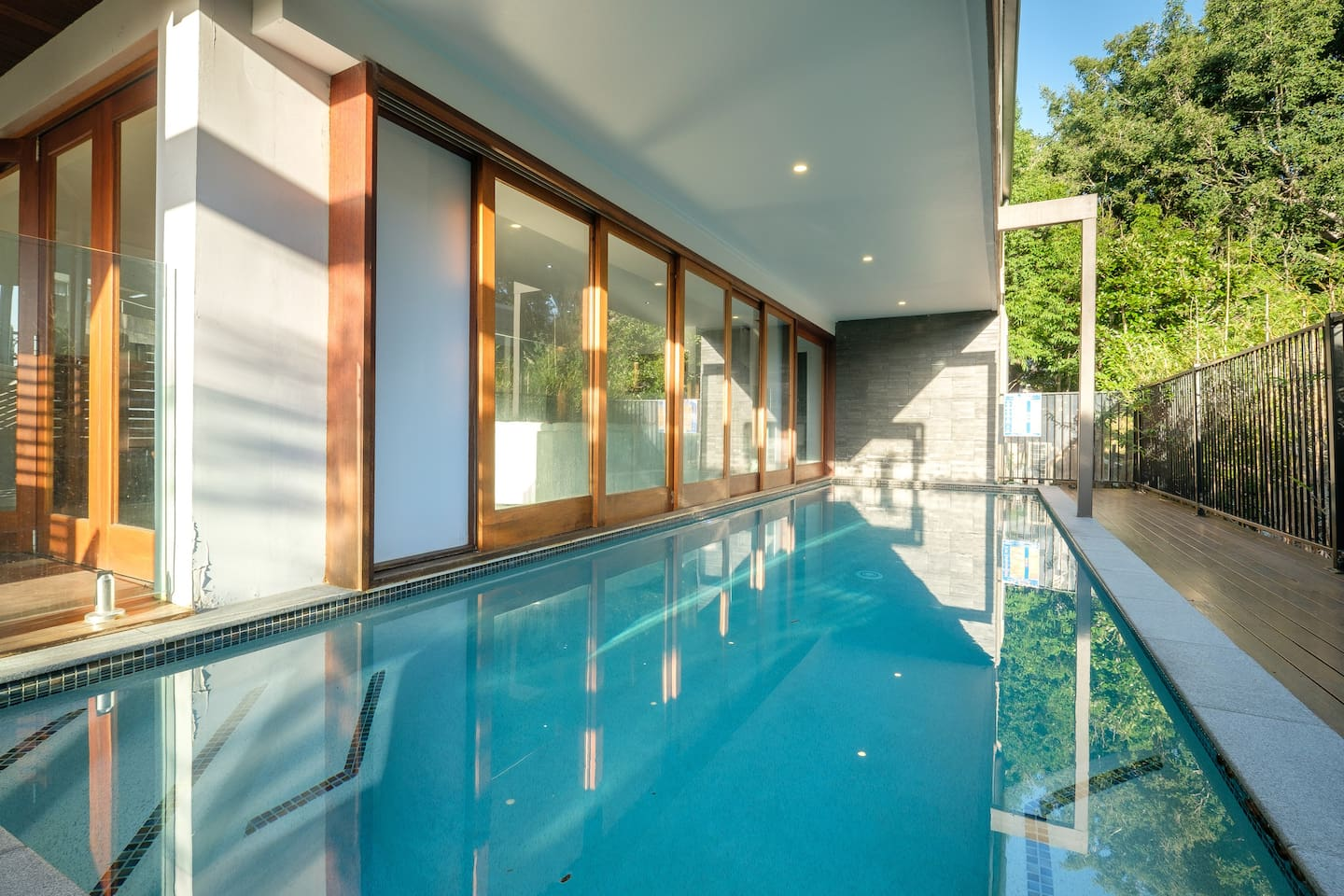Long lap pool with sliding doors opening onto living area