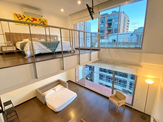 Vista desde las escaleras: En el segundo piso se aprecia la habitación principal con salida al balcón y en el primer piso se aprecia el sofá cama doble armado igualmente con salida al balcón.