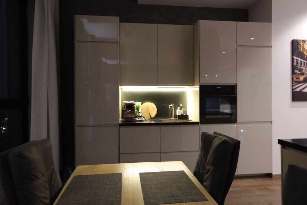 Кухня с холодильником, посудомоечной машиной, духовкой, индукционной плитой, кофемашиной, чайником и тостером.