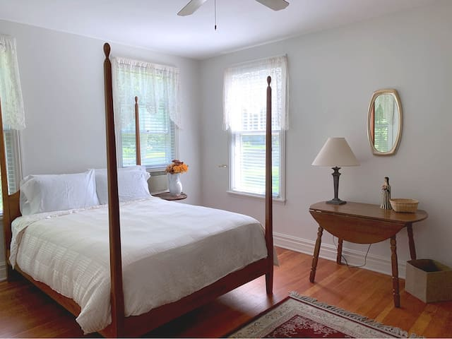 The master bedroom on the 1st floor is bright and sunny with a queen sized bed.