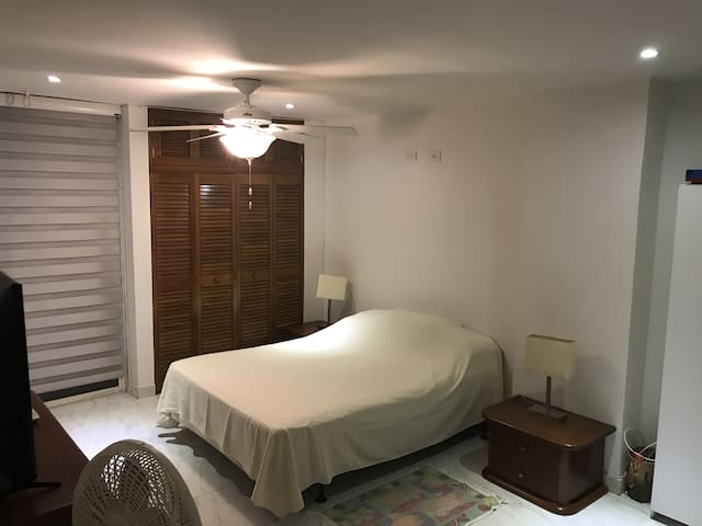 "Cuarto principal con cama doble y escritorio con lámpara. Aire acondicionado, ventilador y TV 42"". Master bedroom with a double bed and a work-desk with lamp. Fan and Air Condition  with 42 in TV."