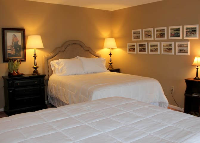 """The master guestroom has two queen beds, blackout curtains over french doors which lead to a porch, a large closet for stowing luggage, and a beautiful vanity area.   We use hotel quality white linens on our """"wonderfully comfortable"""" beds."""